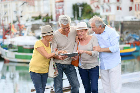 person: Senior couples looking at map on traveling journey Stock Photo