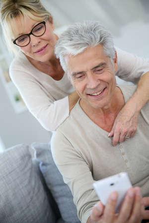 marido y mujer: Pares mayores que miran mensaje en el teléfono inteligente