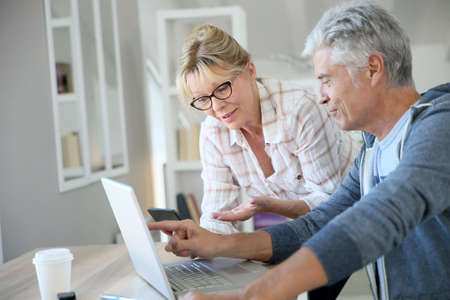 expenses: Senior couple at home checking expenses on internet