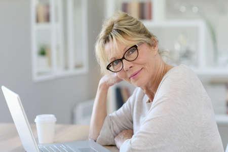 telework: Portrait of senior woman working on laptop computer