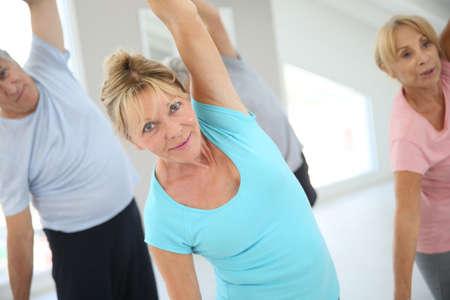 persona mayor: Gente mayor que se extiende en el gimnasio