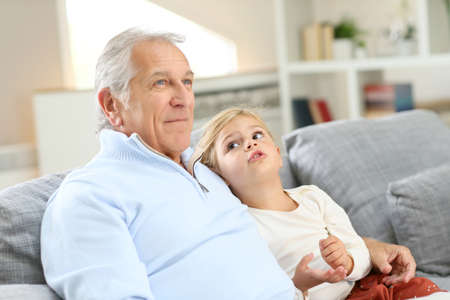 family portrait: Portrait of grandfather with little girl sitting in couch