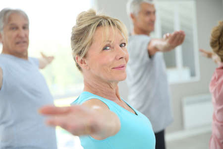 active seniors: Senior people stretching out in fitness room
