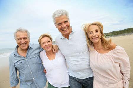 grupo de hombres: Gente mayor que recorre en la playa Foto de archivo