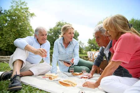 Gruppe ältere Menschen genießen Picknick am sonnigen Tag Lizenzfreie Bilder