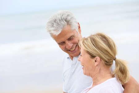 tenderness: Married senior couple walking in the beach