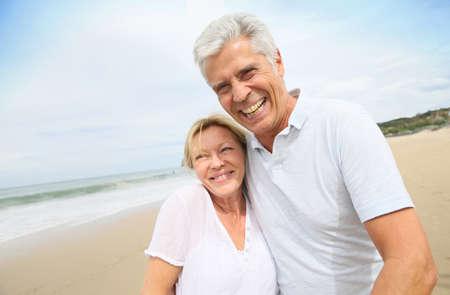 Getrouwd senior paar plezier wandelen op het strand