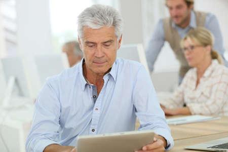 classes: Portrait of senior man working on tablet, training class
