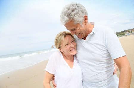 personas abrazadas: Pareja de ancianos Casado divertirse caminando en la playa Foto de archivo