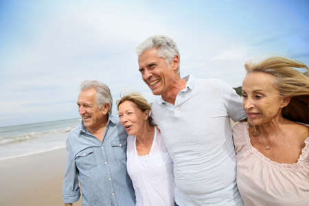 happy seniors: Senior people walking on the beach