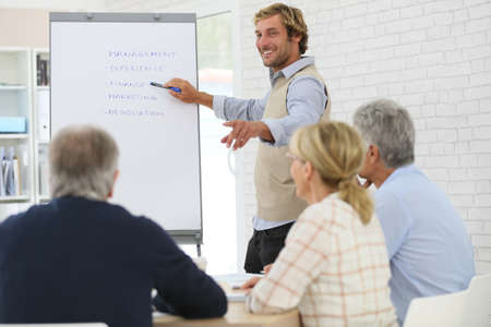 Business instructor leading meeting with senior training group Stock Photo