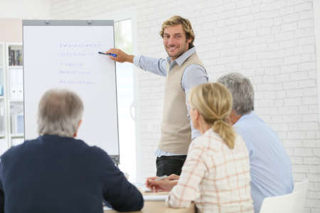 leading: Business instructor leading meeting with senior training group Stock Photo