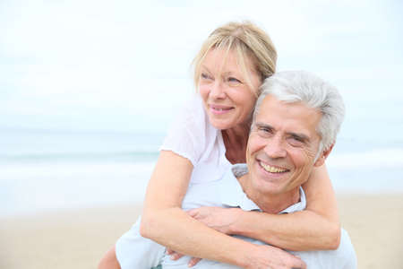 happy old people: Senior man giving piggyback ride to his wife on the beach