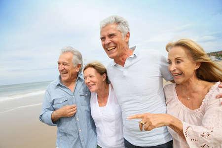 Äldre människor promenerar på stranden