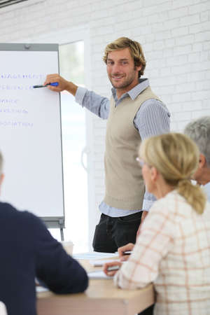 instructor: Business instructor leading meeting with senior training group Stock Photo