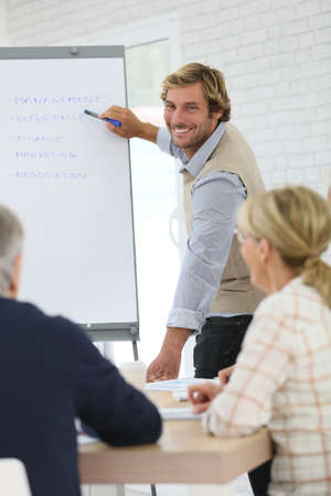 training business: Business instructor leading meeting with senior training group Stock Photo