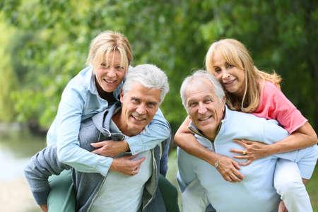 ancianos felices: Hombres mayores que dan a cuestas paseo a mujeres mayores