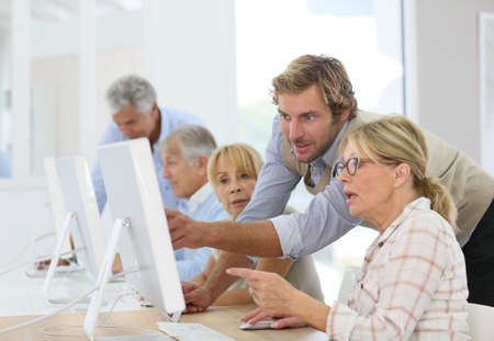 workgroup: Instructor helping senior woman in computing class Stock Photo