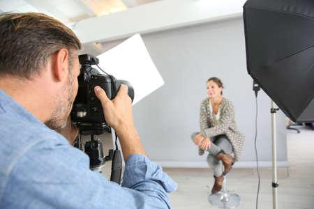 hombre disparando: El fotógrafo en un día de rodaje en estudio con modelo Foto de archivo