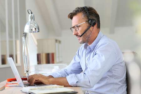 Businessman teleworking, headset on Banque d'images