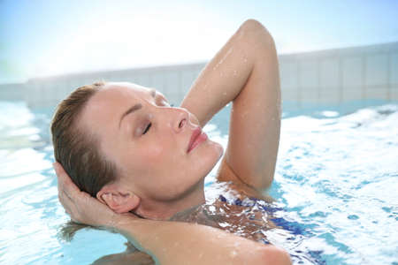 wellness center: Beautiful woman relaxing in hot tub of spa center pool