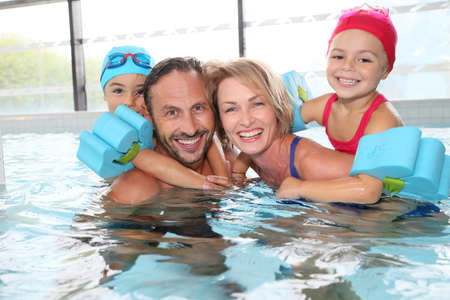 indoors: Portrait of family having fun in public indoor swimming-pool