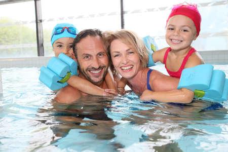 natacion niños: Retrato de la familia que se divierte en la piscina cubierta pública