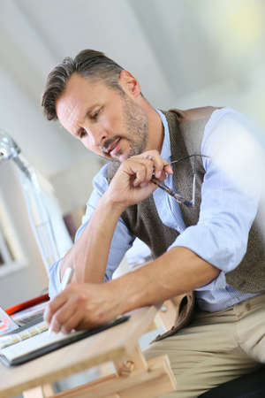 telework: Trendy businessman with eyeglasses writing on agenda