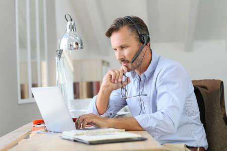 Businessman teleworking, headset on Stock Photo