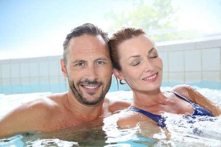 40 years old man: Couple enjoying hot tub bath in spa center