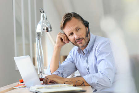 teleworking: Businessman teleworking, headset on Stock Photo