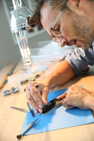 broken telephone: Man repairing broken smartphone in workshop Stock Photo