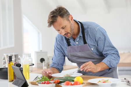 hombre viejo: El hombre en el plato de la cocina de la cocina y el uso de la tableta digital