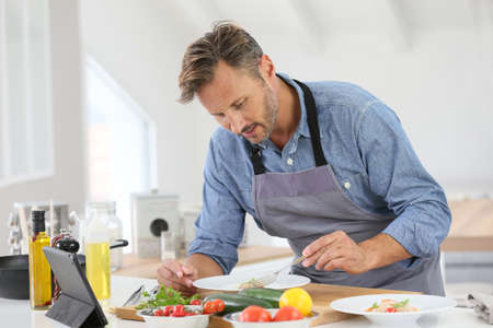 40 years old: Man in kitchen cooking dish and using digital tablet