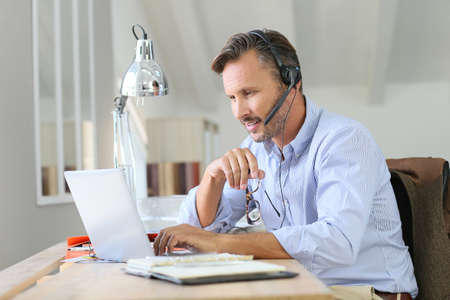 headset business: Businessman teleworking, headset on Stock Photo
