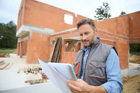Engineer on construction site checking house building with blueprint