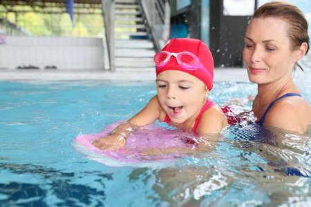 Moeder en dochter opleiding aan het zwembad Stockfoto