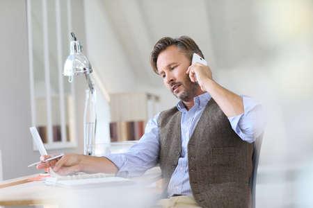 personas trabajando en oficina: Hombre de negocios en el trabajo de hablar por teléfono Foto de archivo