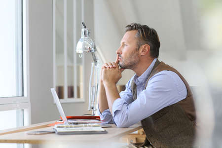 Man in office looking through window, being thoughtful