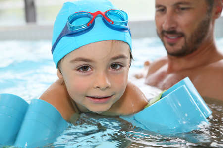 children learning: Little boy learning how to swim Stock Photo