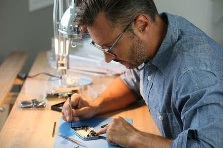 Man repairing broken smartphone in workshop Foto de archivo