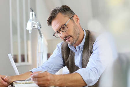 man at work: Trendy businessman with eyeglasses writing on agenda