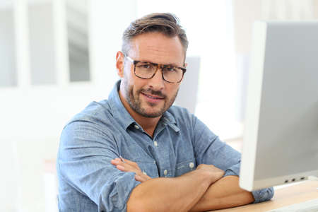 business attire teacher: Handsome man with eyeglasses sitting in front of desktop