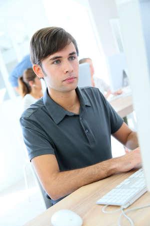 sitting at desk: Student boy in laboratory working on desktop computer