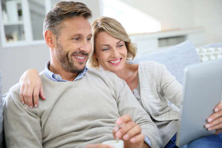 men and women: Middle-aged couple relaxing in sofa and using tablet