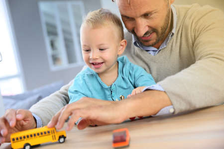carritos de juguete: Pap� con beb� jugando con coches de juguete Foto de archivo