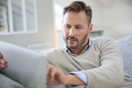 40 years old man: Handsome man at home websurfing on digital tablet