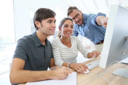 computer science: Teacher with group of students in class working on desktop Stock Photo