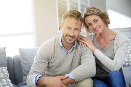 parejas felices: Pareja joven relajante en el sofá de su casa Foto de archivo