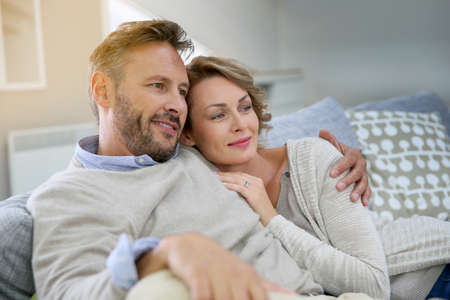 casados: Pareja joven relajante en el sofá de su casa Foto de archivo